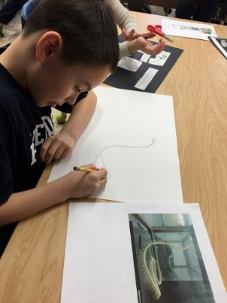 A second grade student creates a scientific illustration of a snake's skeletal system.