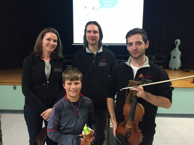 NBSO musicians, Laura Shamu, Peter Zay and Travis Rapoza share a photo with a student following an in-school performance.
